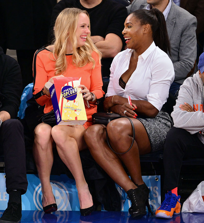 Caroline Wozniacki and Serena Williams laugh together while attending the New York Knicks game against the Washington Wizards at Madison Square Garden on Nov. 4, 2014 in New York City.