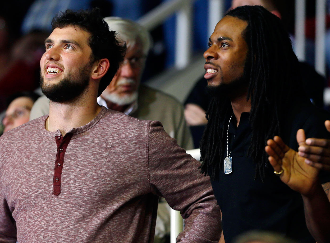 Andrew Luck and Richard Sherman, both Stanford alumni, smile as they watch Stanford's basketball game against Colorado on March 5, 2014 in Stanford, Calif.