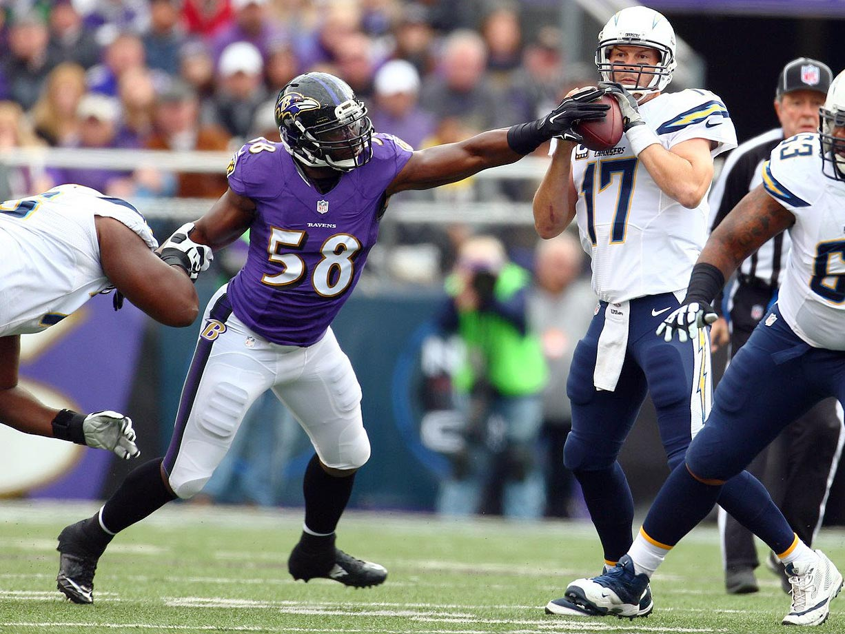 Ravens defensive end Elvis Dumervil looks to strip Philip Rivers during the Baltimore Ravens game against the San Diego Chargers at M&T Bank Stadium in Baltimore on Nov. 30, 2014.