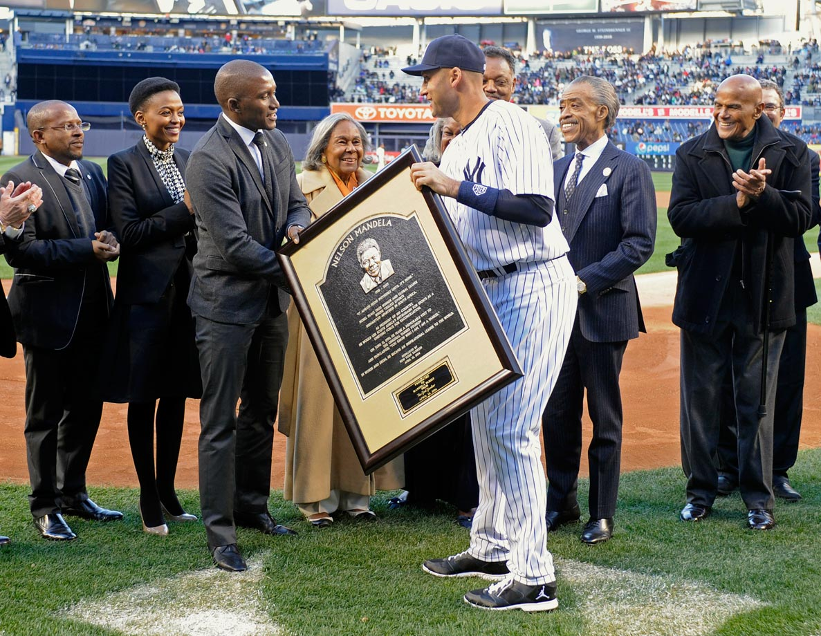 Derek Jeter greets Zondwa Mandela, grandson of Nelson Mandela, with a framed copy of the Nelson Mandela plaque placed in Monument Park at Yankee Stadium before the Yankees game against the Cubs on April 16, 2014.