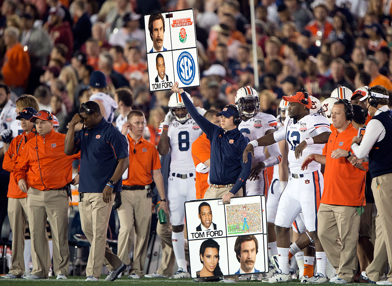 An assistant for the Auburn Tigers holds up play cards with the faces of Ron Burgundy, Jay-Z and Kim Kardashian during the BCS Championship Game between Auburn and the Florida State Seminoles on Jan. 6, 2014 at the Rose Bowl in Pasadena, Calf.