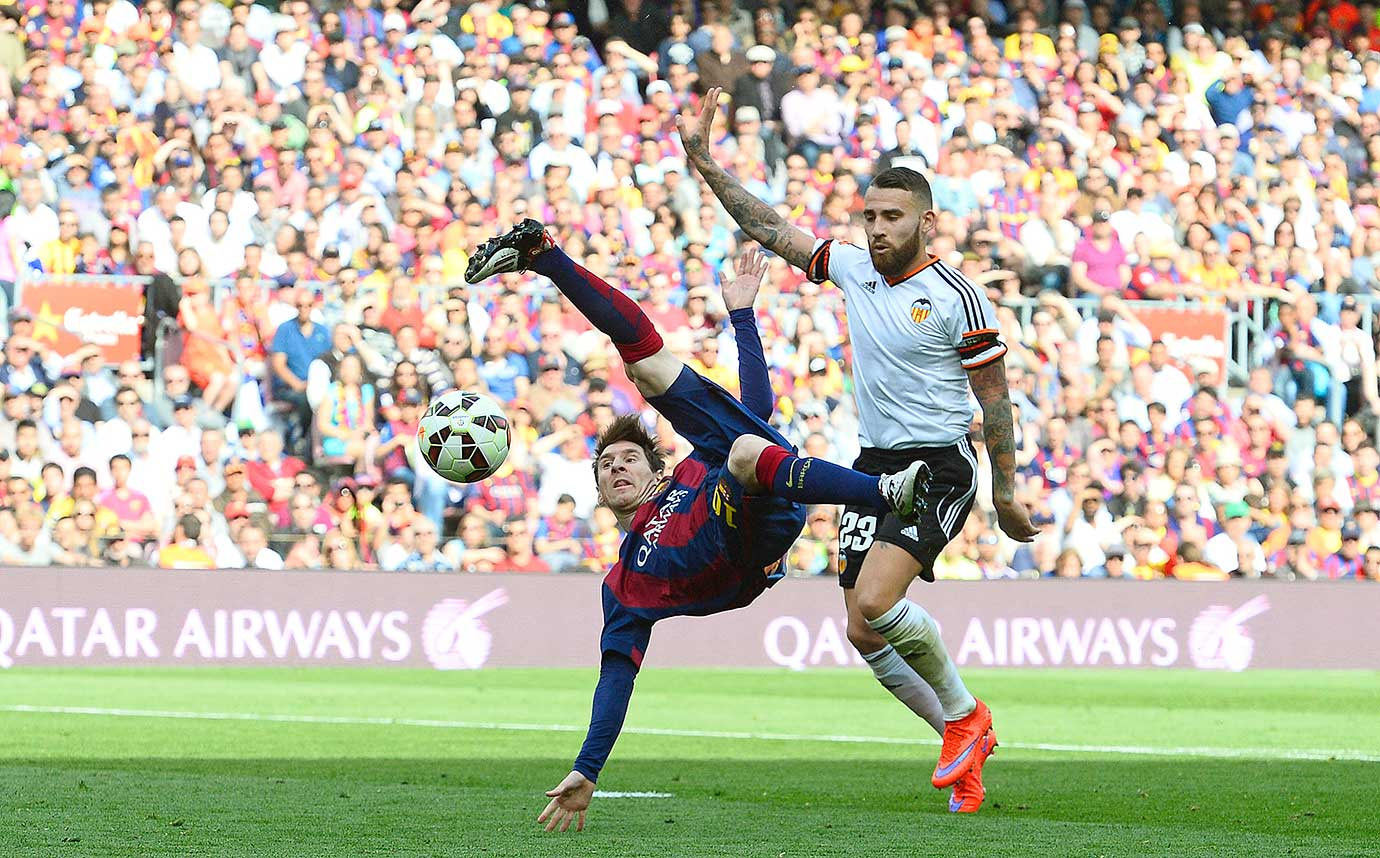 Barcelona's Lionel Messi attempts a bicycle kick against Valencia's Nicolas Otamendi during their La Liga match on April 18, 2015 at the Camp Nou stadium in Barcelona, Spain.
