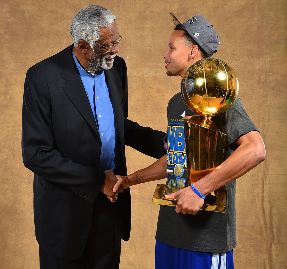 Bill Russell congratulates Golden State Warriors point guard Stephen Curry, holding the Larry O'Brien NBA Championship Trophy, after defeating the Cleveland Cavaliers in Game Six of the NBA Finals in Cleveland.
