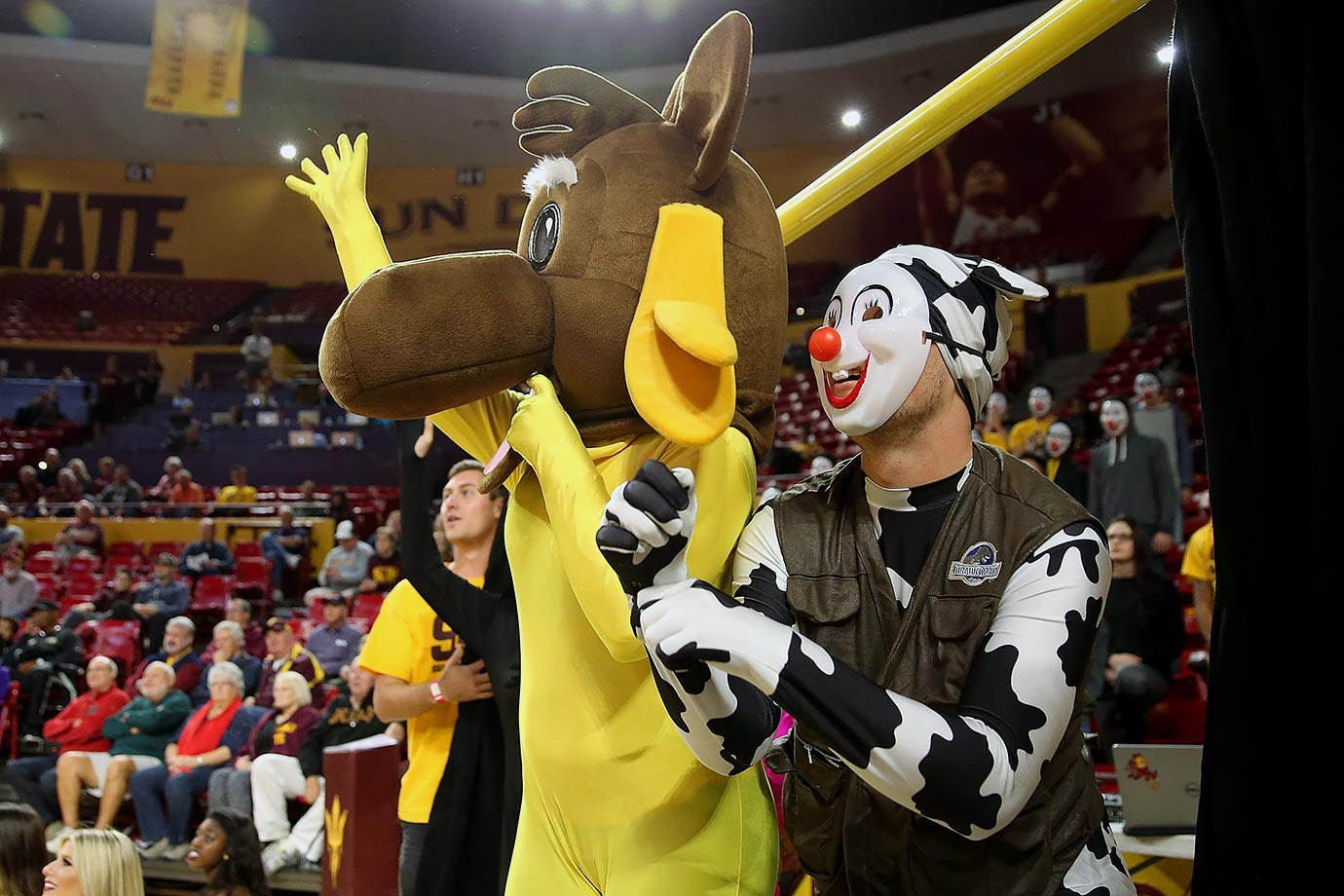 Arizona State hoops fans have the right idea in trying to distract free-throw shooters, who must be confused by what they're looking at — a moose in a yellow unitard and a clown cow?