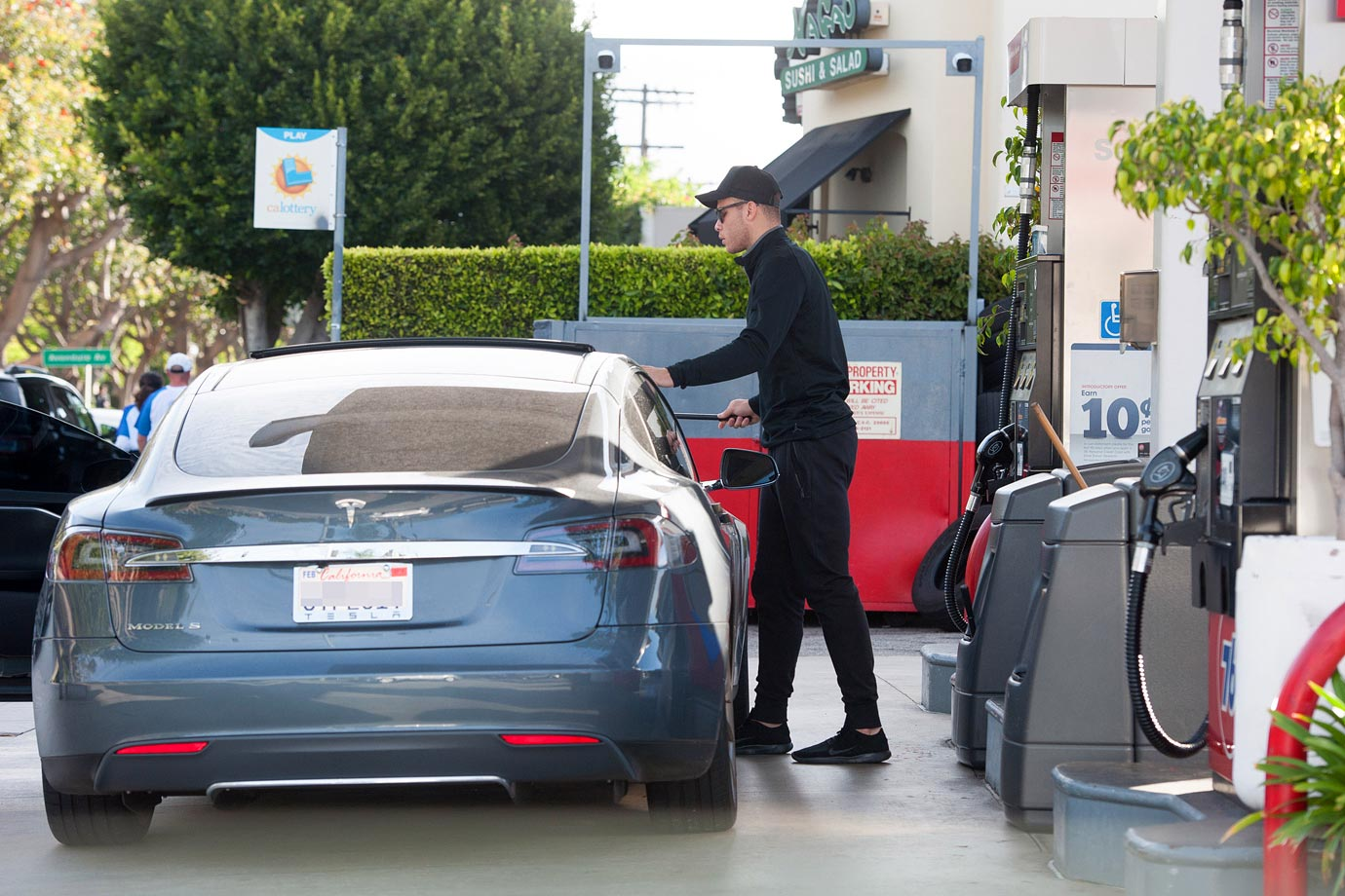 Blake Griffin squeegees the windshield of his Tesla at a gas station in L.A. Not above going to self service.