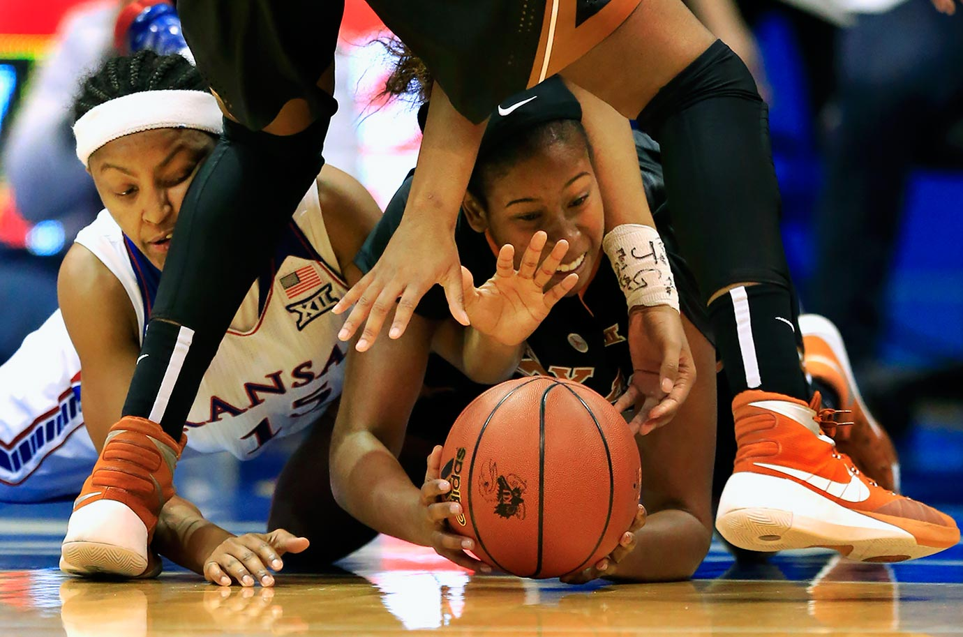 Kansas guard Aisia Robertson and Texas guard Ariel Atkins dive on the floor for a loose ball.