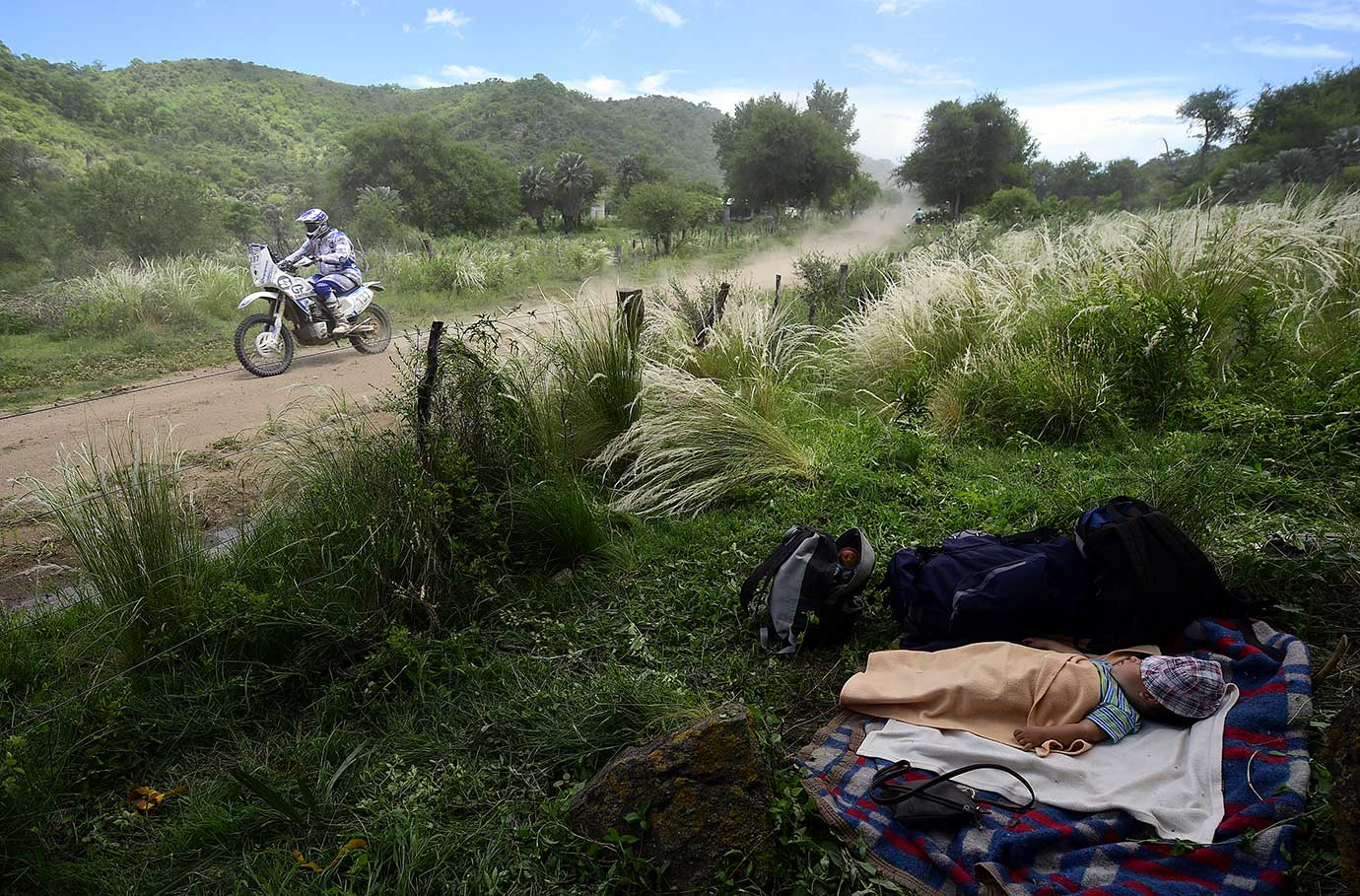 A baby sleeps by the side of a road as a biker competes in the Stage 12 of the Dakar 2016 between San Juan and Villa Carlos Paz in Argentina.