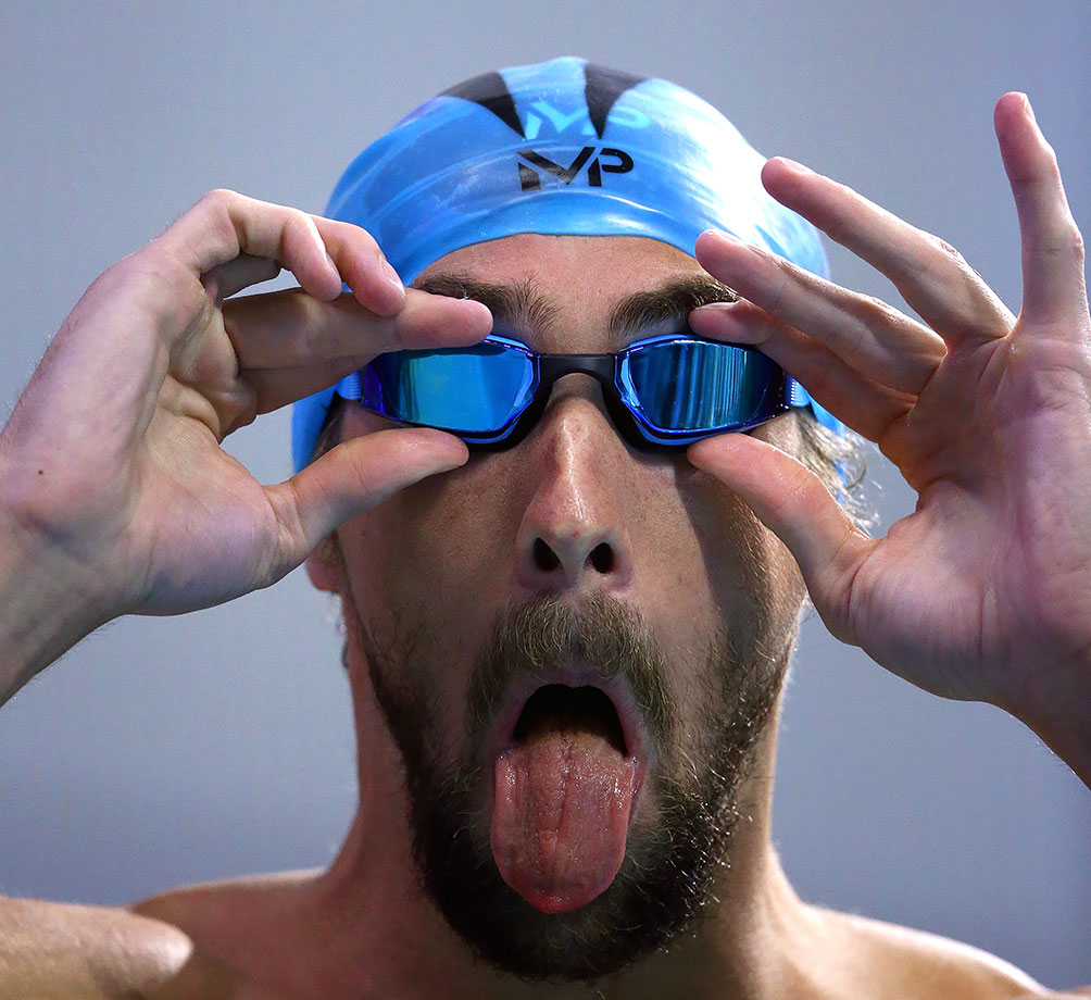 Michael Phelps puts on his game face as he adjusts his goggles before competing in the Men's 100 meter butterfly final in Austin, Texas.