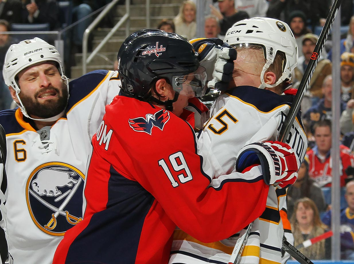 Buffalo Sabres defenseman Mike Weber appears to be causing more harm than good as he gets his glove between teammate Rasmus Ristolainen and Washington Capitals center Nicklas Backstrom.