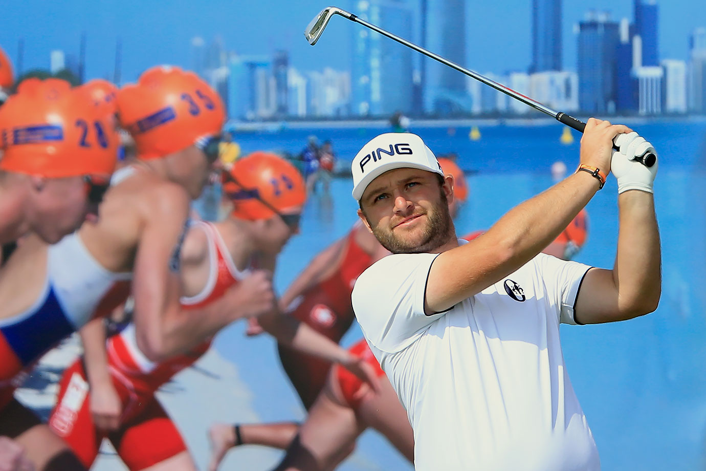 Andy Sullivan appears unfazed by a stampede of swimmers on the billboard behind him as he plays his tee shot on the 15th hole during the second round of the 2016 Abu Dhabi HSBC Golf Championship.