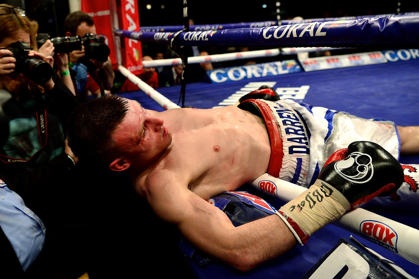 Darren Traynor is knocked through the ropes by Ryan Walsh during their British featherweight title bout at York Hall in London.