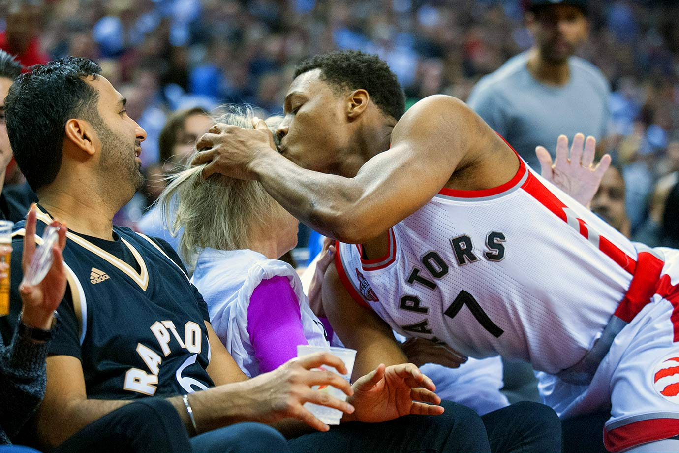 Toronto Raptors point guard Kyle Lowry kisses a fan on the head after running into her while going for a ball off court against the Miami Heat at Air Canada Centre in Toronto.