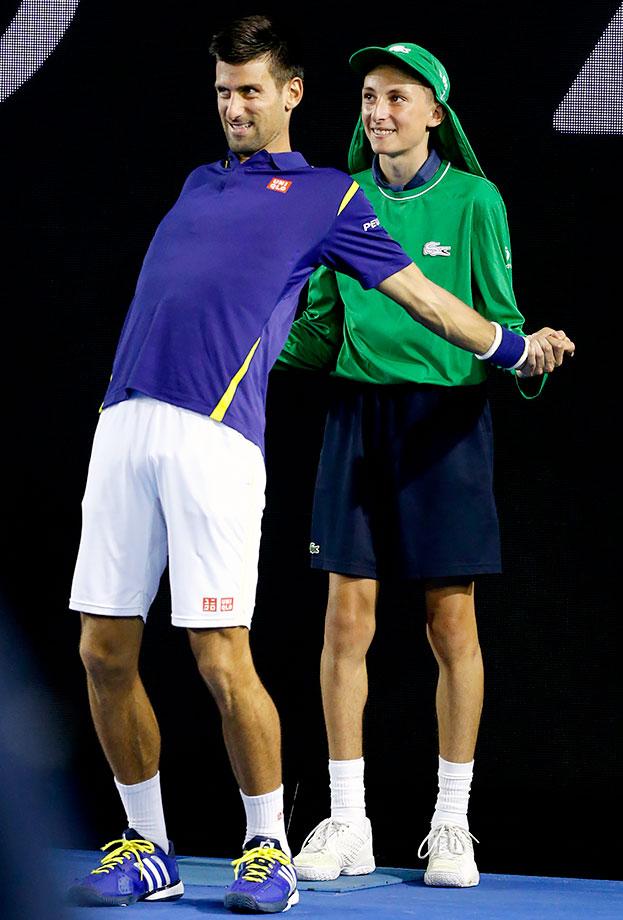 A ball boy helps Novak Djokovic stretch during his quarterfinal match against Kei Nishikori at the Australian Open in Melbourne.