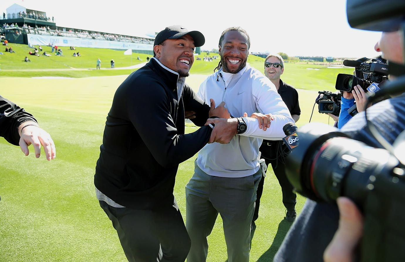 Larry Fitzgerald grabs a reluctant teammate and spectator Michael Floyd to be interviewed after Fitzgerald finished up his round of Pro Am golf in Scottsdale, Ariz.
