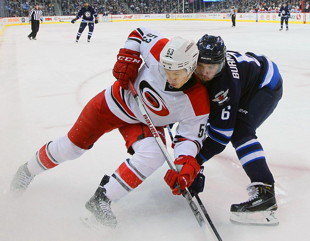 Jeff Skinner and Alex Burmistrov get close as they go into the corner for the puck during a game between the Carolina Hurricanes and Winnipeg Jets at MTS centre in Winnipeg, Manitoba, Canada.