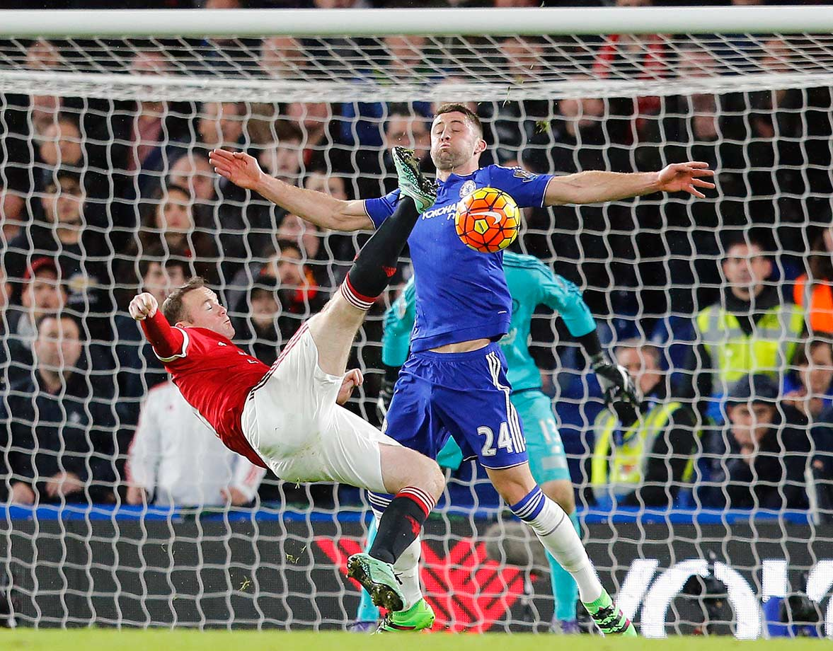 Wayne Rooney gets in a shot despite the challenge of Gary Cahill during the English Premier League match between Chelsea and Manchester United at Stamford Bridge stadium in London.