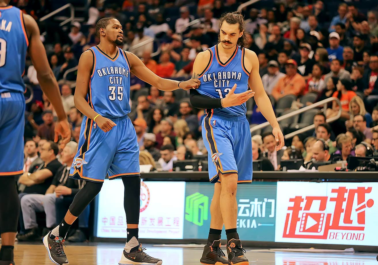 Kevin Durant holds up teammate Steven Adams after his foul during a game between the Oklahoma City Thunder and Phoenix Suns at Talking Stick Resort Arena in Phoenix, Ariz.