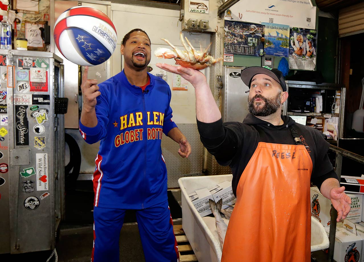 Handles Franklin of the Harlem Globetrotters spins a basketball as market worker Ryan Reese spins a crab at Seattle's famous Pike Place Fish Market.
