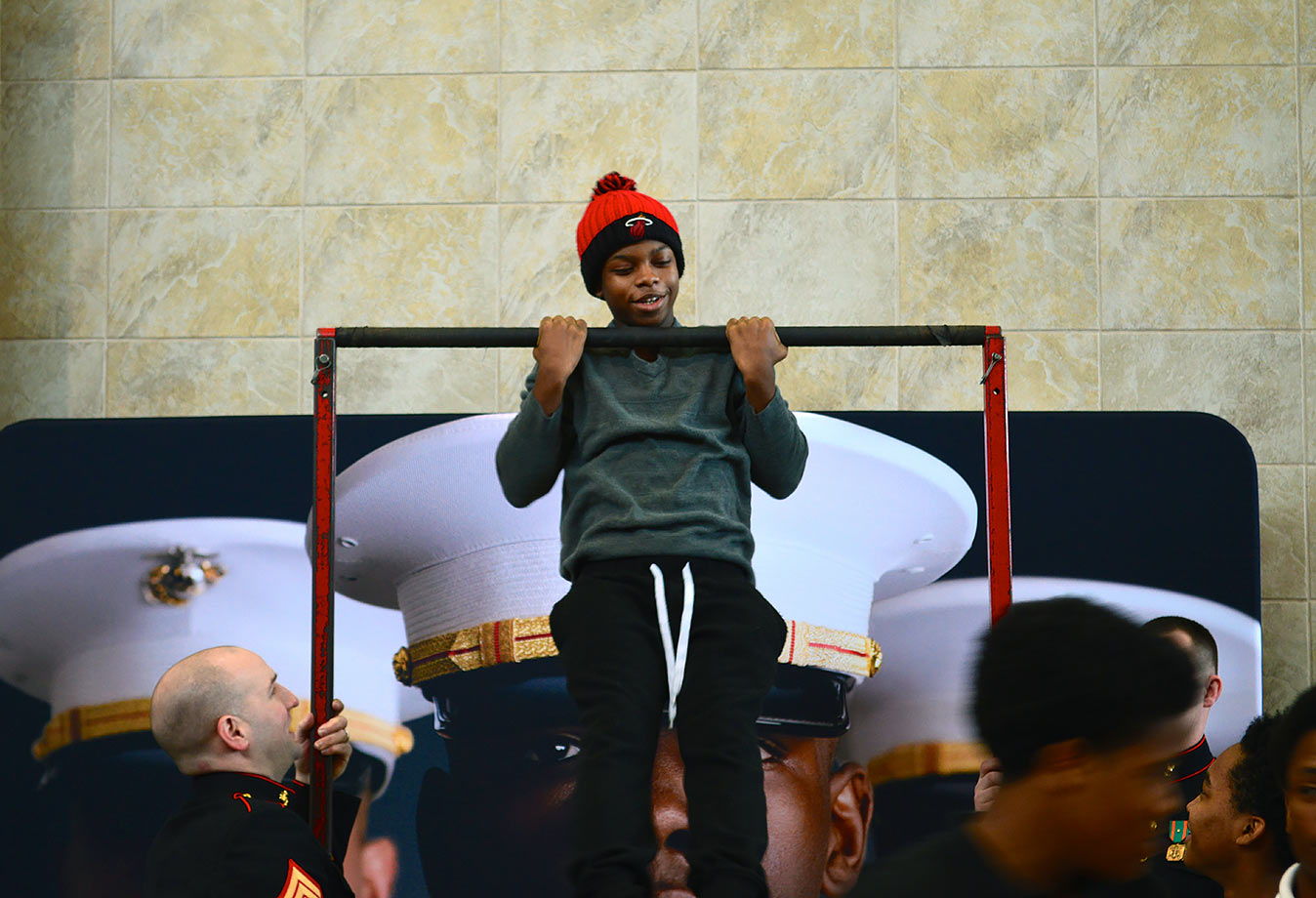 A Harper Woods High student gives it his all in the Marines' pull-up bar challenge.