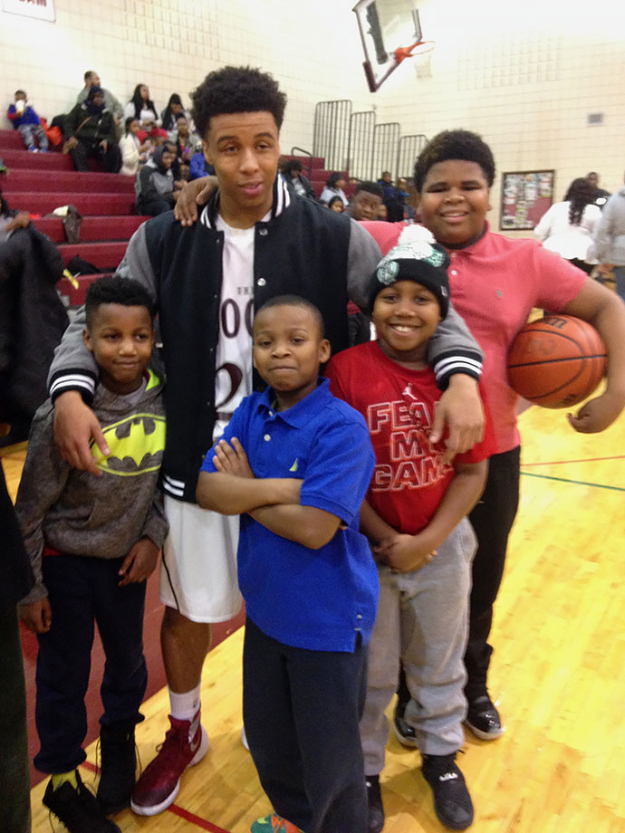 Daijon, who helped build up the N.U.M.E.N. program from a 40-member summer camp to a full-fledged youth league boasting 150 kids from third through tenth grades, poses with some of the children he coaches in the N.U.M.E.N. program.