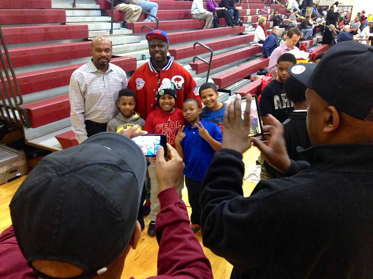 Tim Hardaway Sr. poses with a parent and youth members of N.U.M.E.N.