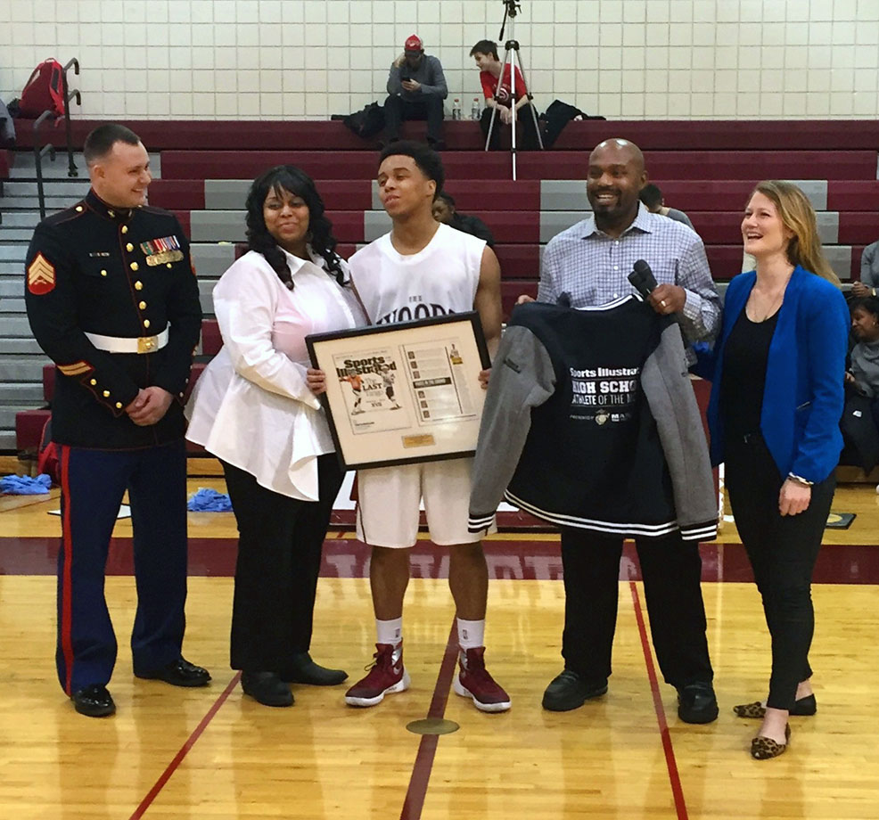 Sgt Jeffrey Frantjeskos of the Marines and Daijon's mother Kashema Smith-McFarland, flank Daijon on the left, while Detroit Pistons assistant coach Tim Hardaway Sr. and editor of the SI High School Athlete of the Month series, Ali Fenwick, help present him with a framed copy of his issue and a letterman's jacket.