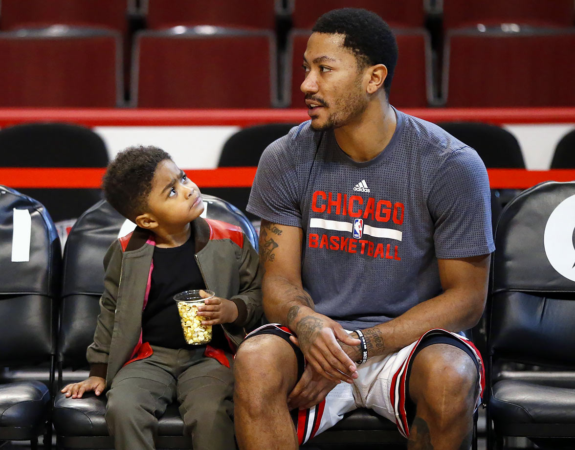 Derrick Rose Jr. looks up to his father before the Chicago Bulls game against the Atlanta Hawks in Chicago.