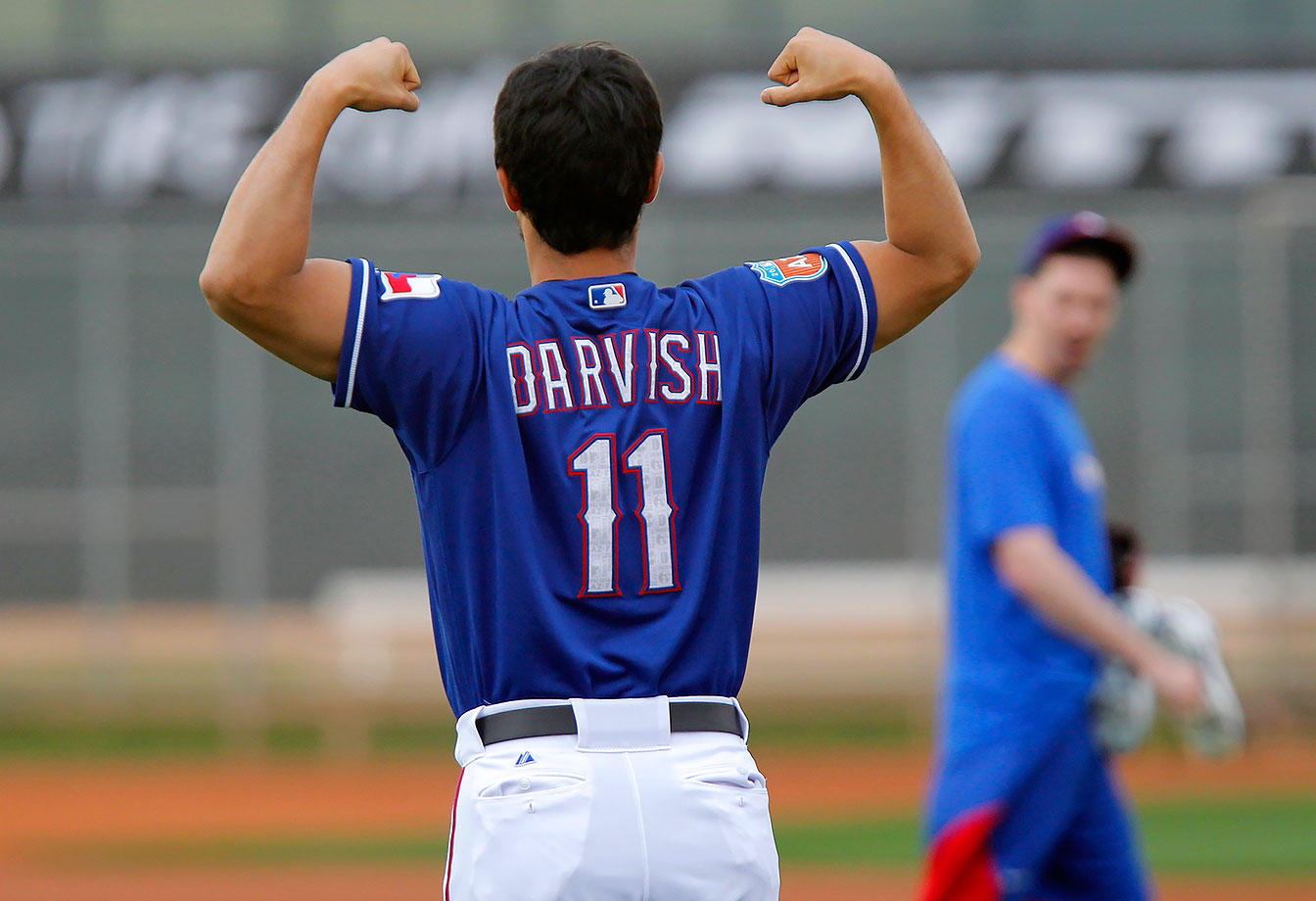 Texas Rangers pitcher Yu Darvish jokes with a teammate as the team begins spring training in Surprise, Ariz.