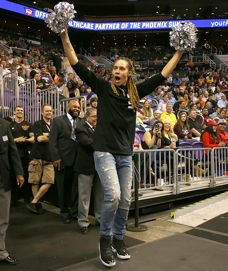 Phoenix Mercury center Brittney Griner cheers with pom-poms during the Phoenix Suns game against the Houston Rockets in Phoenix, Ariz.