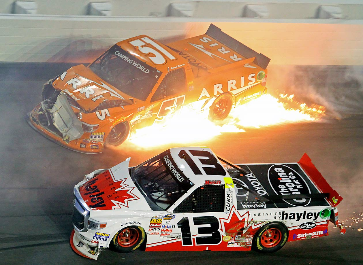 Fire erupts from the truck of driver Daniel Suarez as Cameron Hayley drives past after a crash during the NASCAR Truck Series race at Daytona International Speedway in Daytona Beach, Fla.