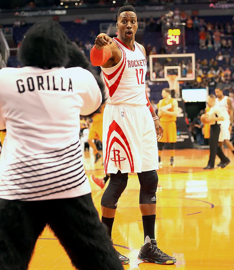 Houston Rockets center Dwight Howard jokes around with the Phoenix Suns Gorilla before a game in Phoenix, Ariz.
