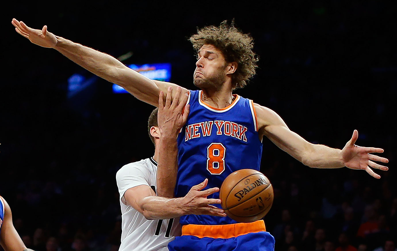 Brooklyn Nets center Brook Lopez passes off the ball around his brother, New York Knicks center Robin Lopez, during the fourth quarter of their game in New York City.