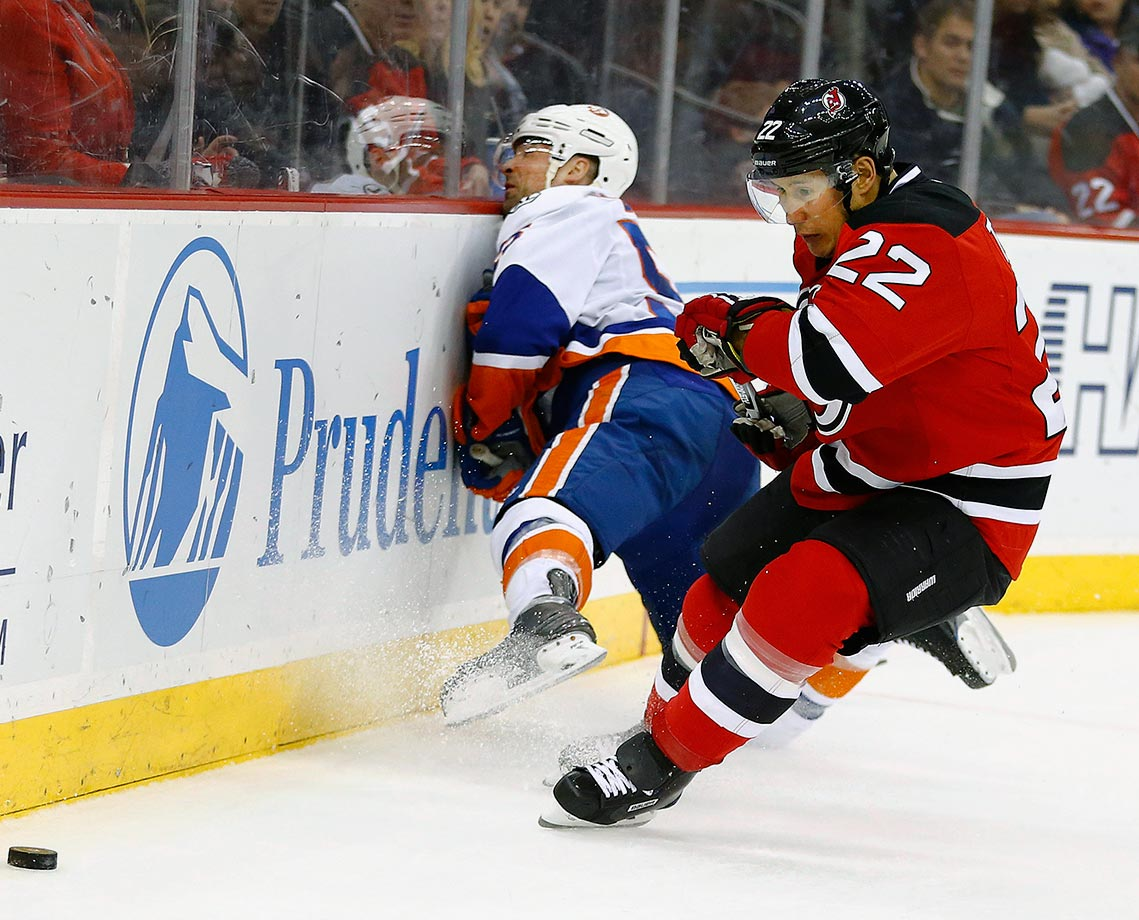 New York Islanders defenseman Johnny Boychuk slams into the boards as New Jersey Devils right wing Jordin Tootoo eyes the puck during the second period of their game in Newark, N.J.