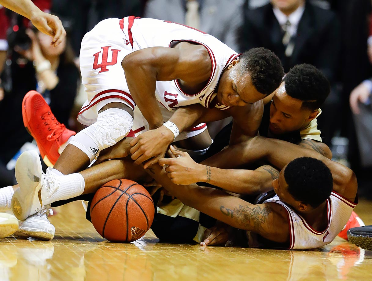 Indiana guard Yogi Ferrell and forward Troy Williams fight for a loose ball with Purdue forward Vince Edwards during the second half of their game in Bloomington, Ind.