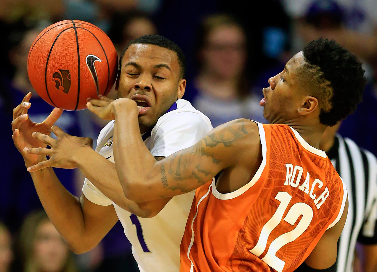 Kansas State guard Carlbe Ervin II is fouled by Texas guard Kerwin Roach Jr. during the first half of their game in Manhattan, Kans.