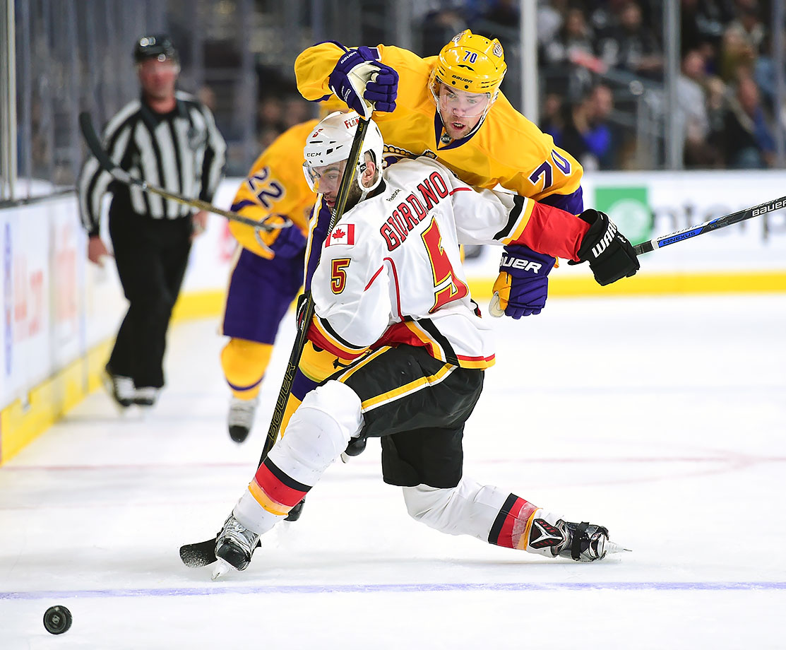 Los Angeles Kings left wing Tanner Pearson is checked by Calgary Flames defenseman Mark Giordano during the second period of their game in Los Angeles.