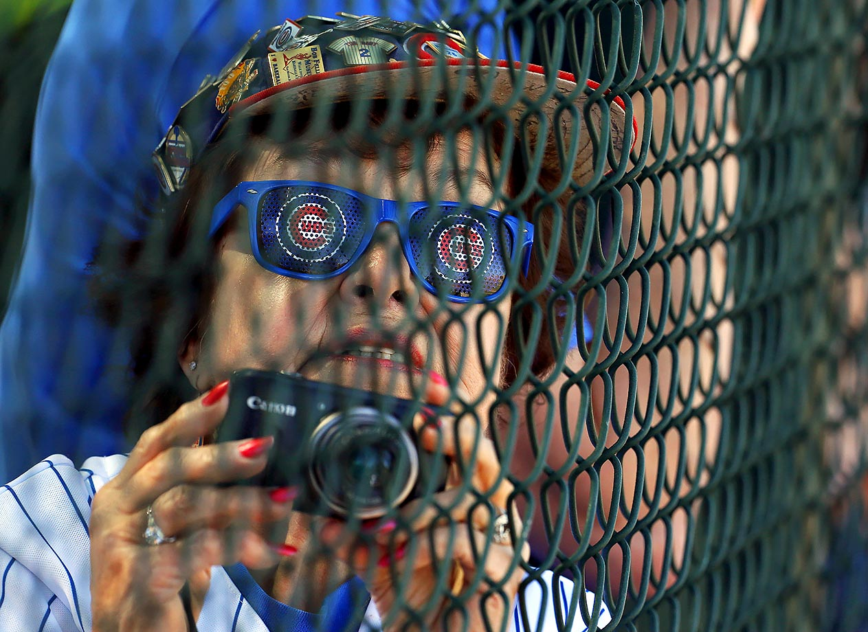 Chicago Cubs fan Kathleen Gray watches the players during a spring training baseball workout in Mesa, Ariz.