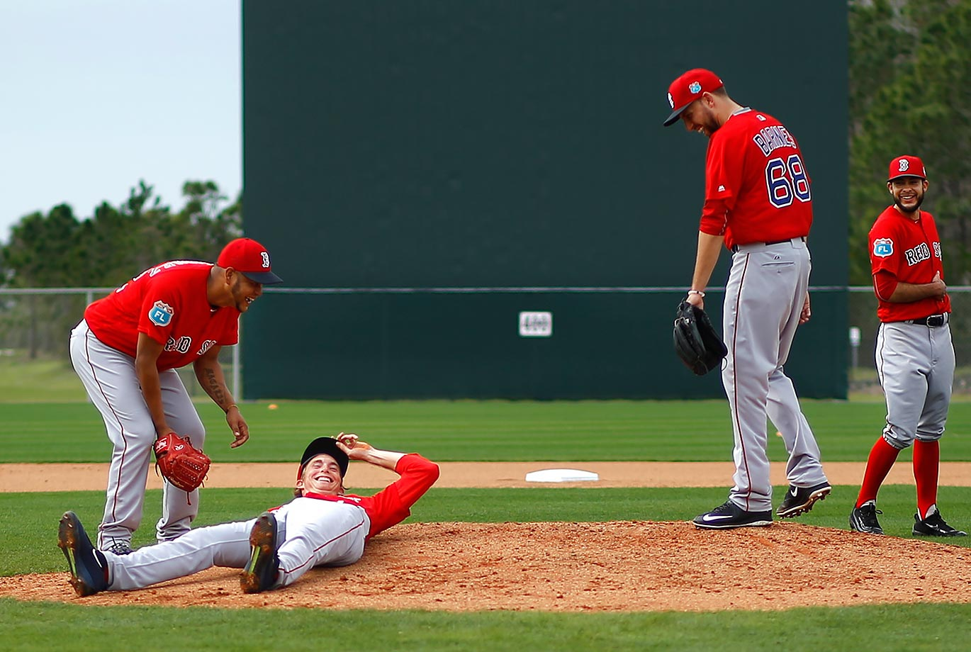 Teammates laugh after Boston Red Sox pitcher Henry Owens stumbled and fell during a fielding drill at a spring training baseball workout in Fort Myers, Fla.