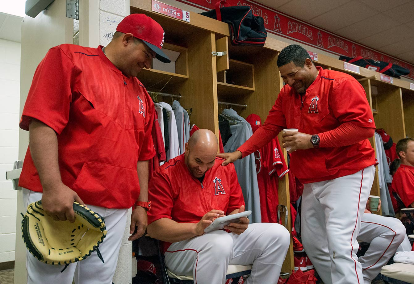 Bengie Molina, Albert Pujols, and Jose Molina of the Los Angeles Angels of Anaheim joke in the locker room before spring training in Tempe, Ariz.
