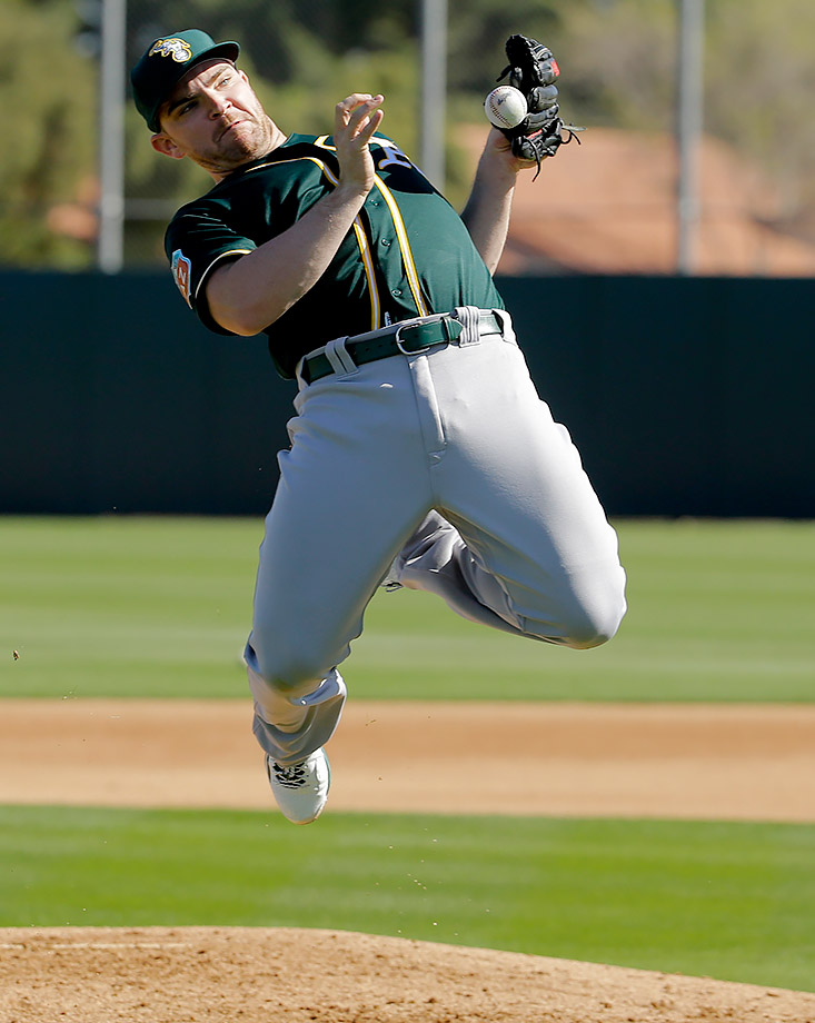 Oakland Athletics pitcher Liam Hendriks reacts to a ball hit at him, which he managed to catch in his non-glove hand, during spring baseball practice drills in Mesa, Ariz.