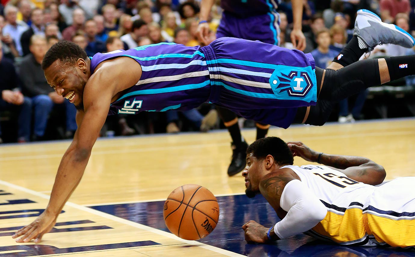 Charlotte Hornets guard Kemba Walker leaps over Indiana Pacers forward Paul George as they chase a loose ball during the second half of a game in Indianapolis.
