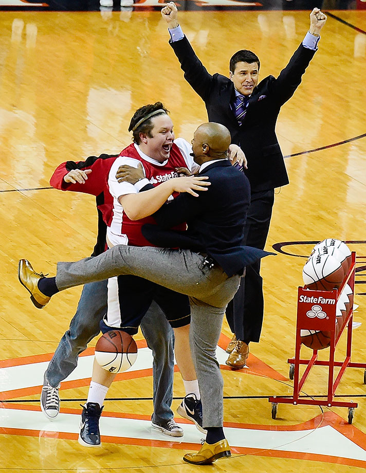 Andrew Board celebrates with ESPN College GameDay host Jay Williams after making a half-court shot for $18,000 during a live broadcast before a game between North Carolina and Virginia in Charlottesville, Va.