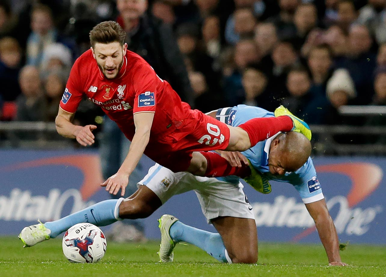 Liverpool's Adam Lallana competes for the ball with Manchester City's Vincent Kompany during the English League Cup final match in London.