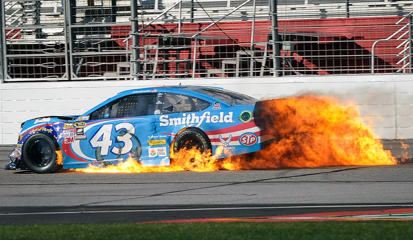 Aric Almirola's car catches fire on the front stretch near the end of a NASCAR Sprint Cup Series race at Atlanta Motor Speedway in Hampton, Ga.