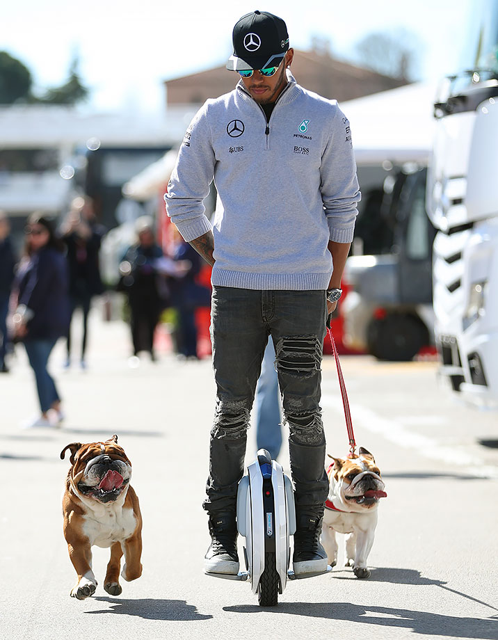 Lewis Hamilton arrives in the paddock with his dogs Roscoe and Coco during day one of F1 winter testing at Circuit de Catalunya in Montmelo, Spain.