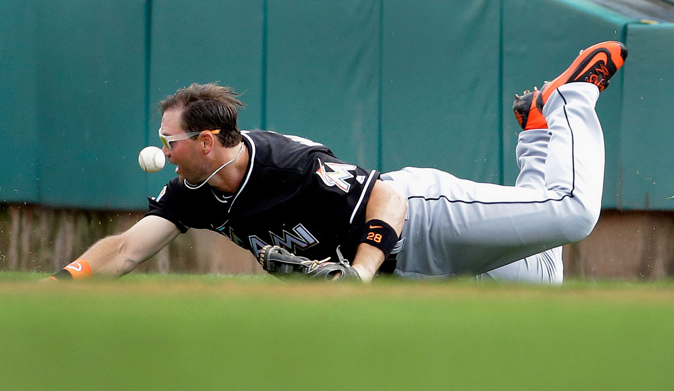 Miami Marlins right fielder Cole Gillespie dives but cannot catch a single hit during the third inning of an exhibition spring training game against the St. Louis Cardinals in Jupiter, Fla.