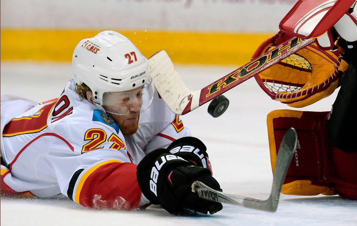 Calgary Flames defenseman Dougie Hamilton slides across the goal crease to knock away the puck during the third period of a game against the Buffalo Sabres in Buffalo, N.Y.