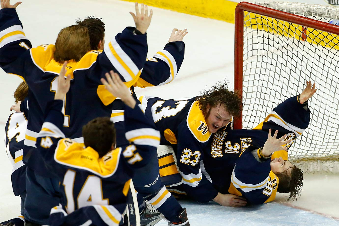 Wayzata defenseman Hank Sorensen and teammates pile on goalie Alex Schilling after the team defeated Eden Prairie 5-3 to win the boys' Class AA state hockey tournament championship game in St. Paul, Minn.