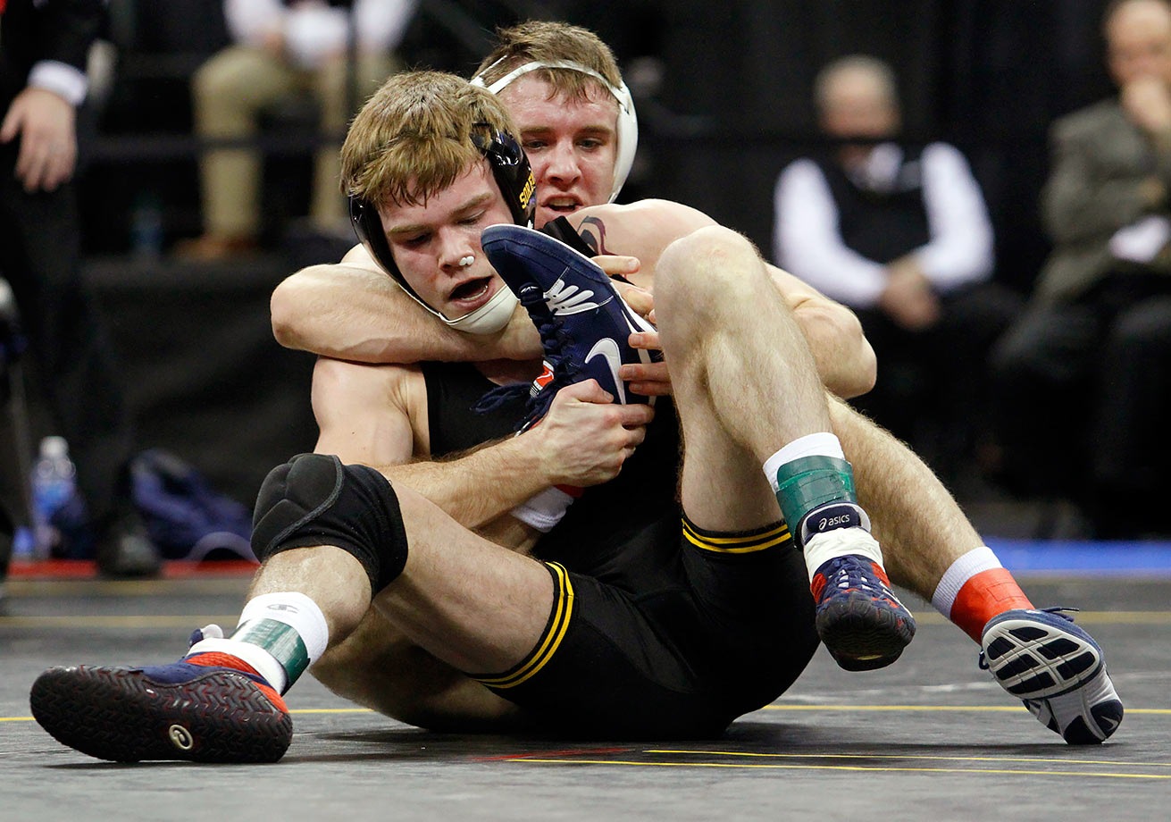 Iowa's Brandon Sorensen grabs the foot of Penn State's Zain Retherford as the two compete in the 149-pound weight class finals during the Big Ten wrestling championships in Iowa City, Iowa.