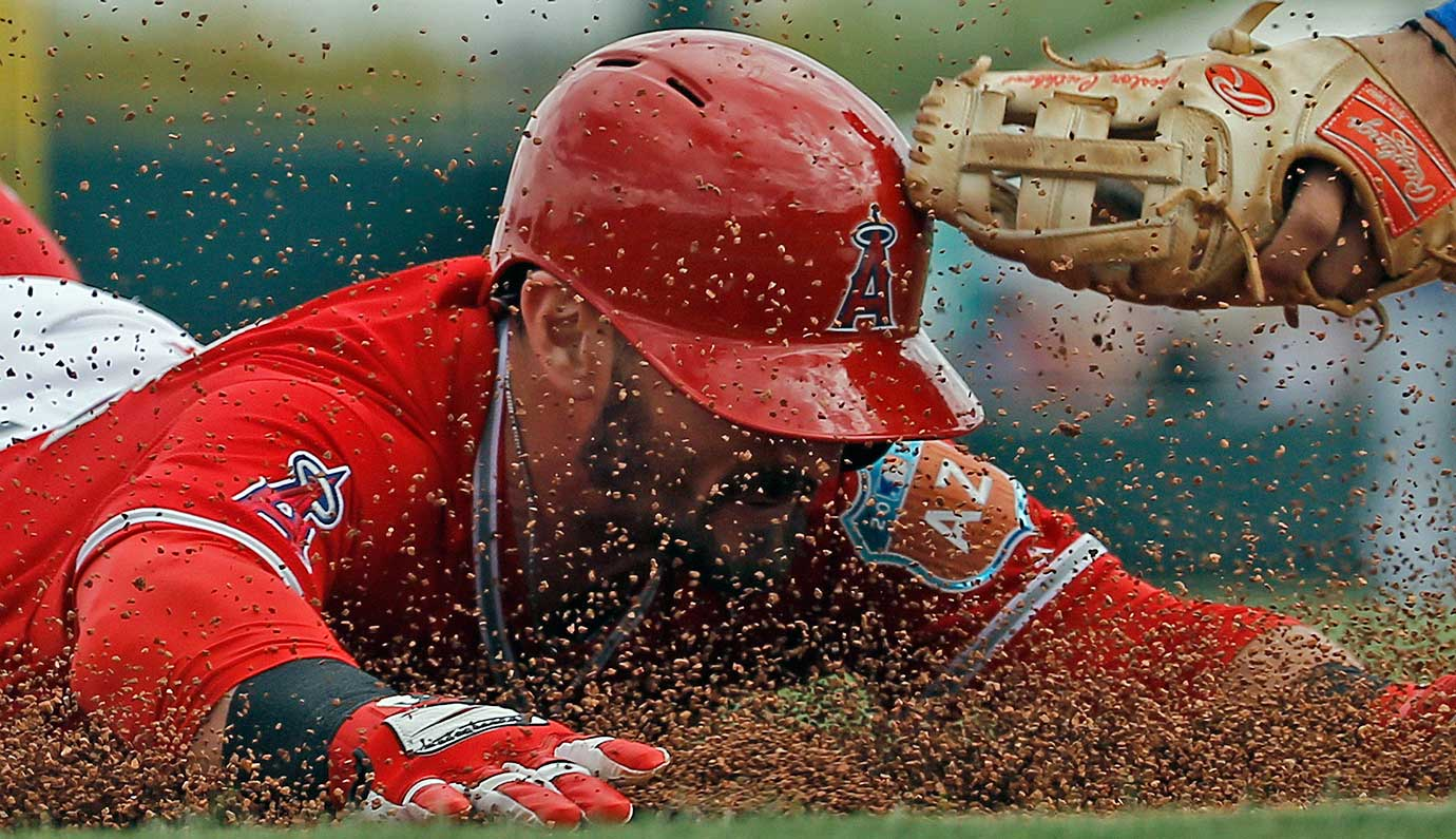 Los Angeles Angels second baseman Johnny Giavotella slides safely for a triple during the second inning of a spring training game against the Kansas City Royals in Tempe, Ariz.